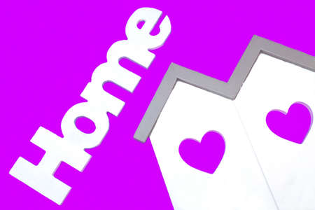 violet residential: White Small House Wooden Model  With Two Windows In The Shape Of A Heart And Sign Home Isolated On The Purple Background, Close Up
