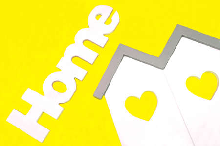 residential house: White Small House Wooden Model  With Two Windows In The Shape Of A Heart And Sign Home Isolated On The Yellow Background, Close Up