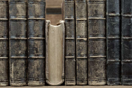 black leather texture: Old Shabby Books With Black Leather Cover On The Bookshelf Horizontal Background Texture