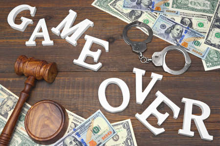 confiscation: Sign Game Over, Money, Real Handcuffs, Judges Gavel On The Wood Rough Table Background. Concept For  Bankruptcy, Gambling, Fraud, Bribe, Bail, Illegal Income, Tax Stock Photo