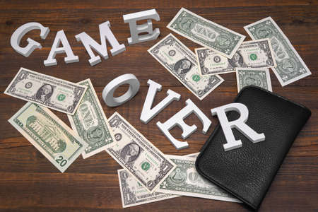 payola: Sign Game Over Dollars And Empty Purse On Wood Background. Concept For  Bankruptcy, Gambling, Fraud, Bribe Stock Photo