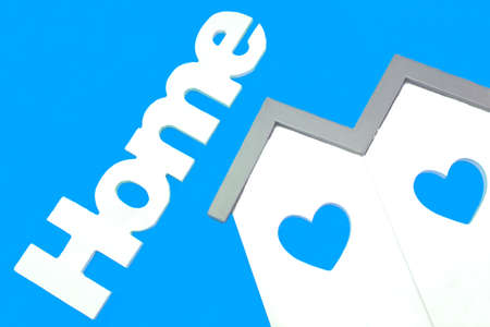 roof house: White Small House Wooden Model  With Two Windows In The Shape Of A Heart And Sign Home Isolated On The Light Blue  Background, Close Up Stock Photo
