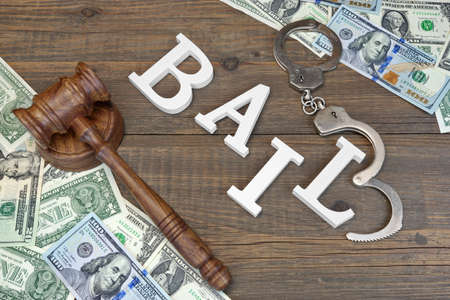 bail: Judges Gavel, White Sign BAIL From Wooden Letters, Real Police Shabby Handcuffs And American Dollar Cash On Rough Wood Background, Top View Stock Photo