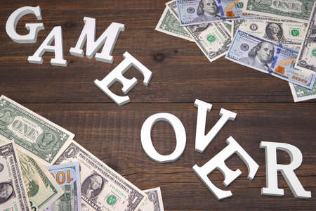 payola: Sign Game Over And Dollars Bills On The Wood Background. Concept For  Bankruptcy, Gambling, Fraud, Bribe