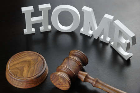 real estate house: Judges Or Auctioneer Gavel And White Sign Home Made From Wooden Letter On Black Wood Table  Background In Back Light, Close Up, Conceptual Image. Stock Photo
