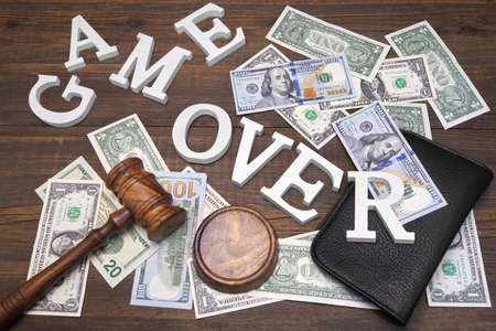 forfeiture: Sign Game Over, American Dollars Cash  Judges Gavel On The Wood Rough Table Background. Concept For  Bankruptcy, Gambling, Fraud, Bribe, Bail, Illegal Income, Tax Stock Photo