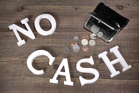 joblessness: No Cash Sign Made From White Wood Letter And Empty Black Purse With Different British Coins On The Rough Wood Background, Top View, Conceptual Image