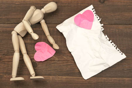 spat: Wood Humane Figurine, Torn Blank ?rumpled Paper Page And Two Broken Hearts On The Wood Background