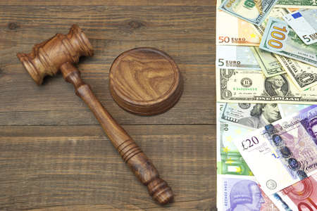 international money: Judges Walnut Gavel And International Money (Dollars, Euro, Pound Sterling) On Rough Wood Background. Overhead View. Conceptual Image