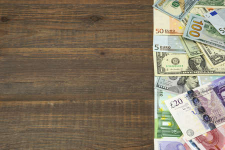 international money: International Money (Dollars, Euro, Pound Sterling) On Rough Wood Background. Overhead View. Conceptual Image
