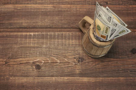 tax tips: American Dollar Bills In The Wood Bear Mug Top View On The Rough Wooden Table Background With Copy Space Stock Photo