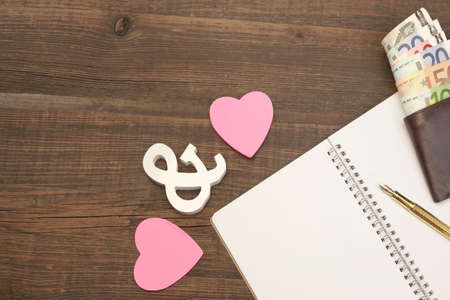 dowry: Wedding Costs Concept Image. Hearts, Gold Pen, Notepad With Blank Paper, Male Wallet With Dollar Cash On The Wood Background With Copy Space, Top View