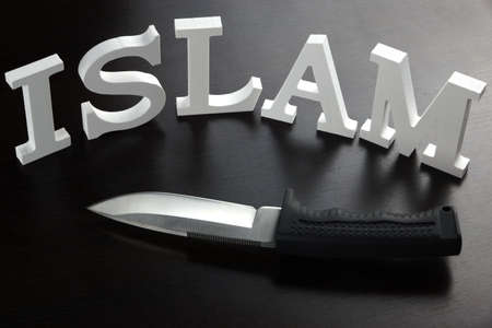 caliphate: White Sign ISLAM (Islamic State of Iraq and the Levant) Made From Wood Letter And Military Knife On The Black Table Background, Close Up, Concept