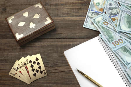 cards deck: Opened Notepad With Blank White Page, Fountain Pen, Dollar Cash And Two Unopened Playing Cards Deck In Box On Wood Table Background With Space, Top View
