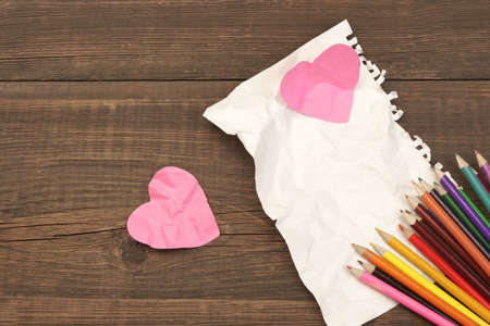 unrequited love: Unrequited Love Concept. Many Color Pencils, Two Crumpled Broken Heart And Blank Page On The Wood Background, Copy Space, Top View Stock Photo