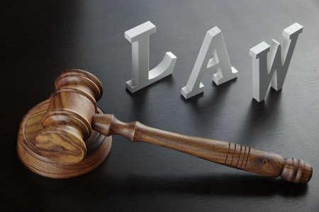 martillo juez: Mazo de los jueces y negro registrada de la ley Hecho de madera de la letra En El Fondo Negro mesa de madera en la luz trasera, de primer plano, imagen conceptual. Foto de archivo