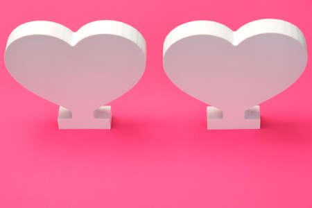 couple background: Two White Wooden Heart On The Pink Paper Background, Close Up, Top View