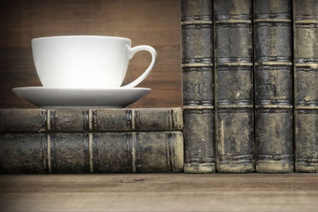 antique books: Old Shabby Books In Stack And White Empty Cup On The Rough Wood Horizontal Background With Copy Space