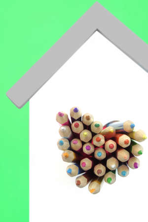 green and white: A Lot Of Sharped Colored Pencils Are Sticking Out From The Heart Shaped Window In The Home White Wall Isolated On Green Background, Vertical Image