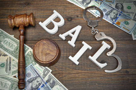 court room: Judges Gavel, White Sign BAIL From Wooden Letters, Real Police Shabby Handcuffs And American Dollar Cash On Rough Wood Background, Top View Stock Photo