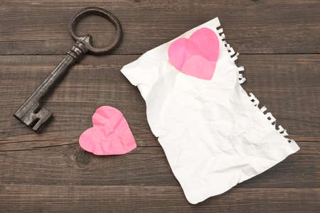 unrequited love: Unrequited Love Concept. Vintage Key, Two Crumpled Broken Heart And Blank Page On The Wood Background, Copy Space, Top View Stock Photo