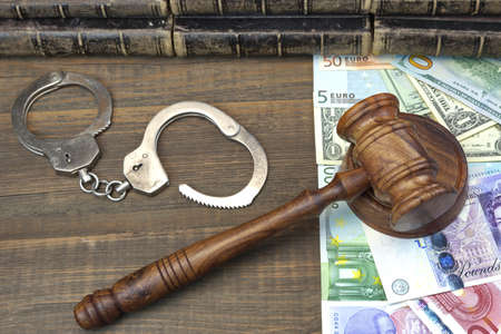international money: Judges Walnut Gavel, Handcuffs And International Money (Dollars, Euro, Pound Sterling) On Rough Wood Background. Overhead View. Conceptual Image Stock Photo