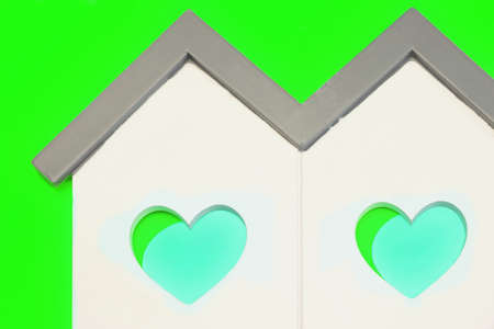 green background: White Home Wooden Shape With Two Blue Green Heart Shape Window Isolated Background, Concept