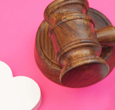 marido y mujer: legalities Of Divorce Concept. Judges Gavel And Two White Hearts Isolated On Pink Background. Top View Foto de archivo