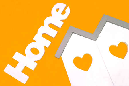 residential house: White Small House Wooden Model  With Two Windows In The Shape Of A Heart And Sign Home Isolated On The Orange Background, Close Up