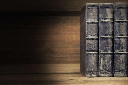 libros antiguos: Tres viejos libros viejos con la cubierta de cuero negro en la estantería de madera Fondo horizontal con espacio de copia Foto de archivo