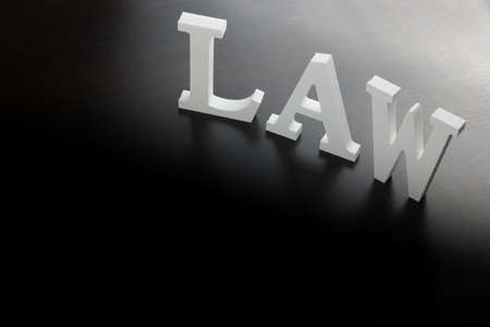 solicitor: White Sign Law Made From Wooden Letter On The Black Wood Table  Background In Back Light, Close Up, Conceptual Image.