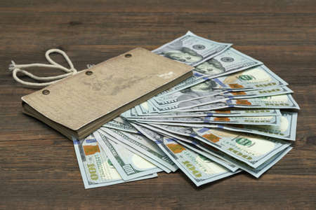 fine tip: Vintage Notebook With American Dollar Cash On Rough Rustic Brown Wood Table Background