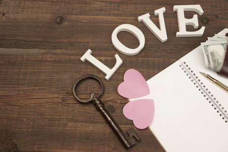 dowry: Wedding Concept Image. Hearts, Gold Pen,Vintage Key, Notepad With Blank Paper, Male Wallet With Dollar Cash On The Wood Background With Copy Space, Top View