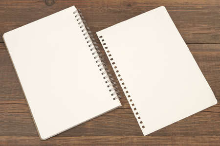 snatched: White Spiral Notepad And Single Torn  Blank Page On Rough Brown Wood Background, Top View, Close Up Stock Photo