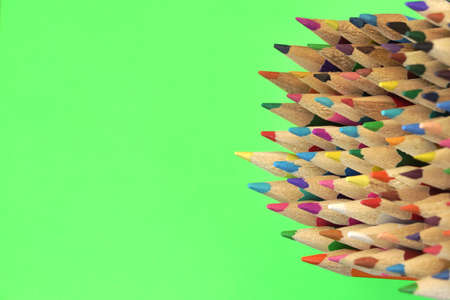 green concept: Large Group Of Wood Colored Pencil Isolated On Green Vertical Background. Concept For Education, Children Creativity, Art Work, Drawing Stock Photo