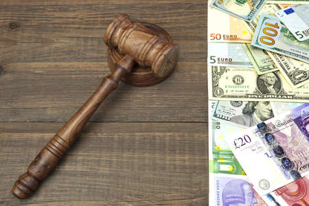 graft: Judges Or Auctioneers Gavel And International Cash - Dollars, Euro, Pounds On Rough Brown Wood Table Background With Space For Text Or Image