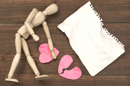 fracas: Wood Humane Figurine, Torn Blank ?rumpled Paper Page And Two Broken Hearts On The Wood Background