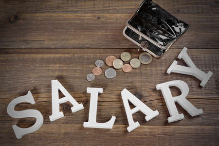 joblessness: Salary Sign Made From White Wood Letter And Empty Black Purse With Different British Coins On The Rough Wood Background, Top View, Conceptual Image
