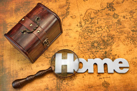 portmanteau: Home Search Or Emigration Concept. Bag Or Storage Box, Wooden Sign Home And Magnifier On the Old Map Background, Top View, Close Up Stock Photo