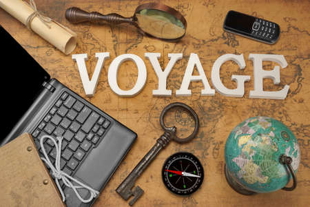 gsm: Wooden Sign Voyage, Laptop With Blank Display, Retro Key, Vintage Globe And Magnifier, Modern Compass, GSM Phone And Letter On The Old Map, Flat Lay, Top View