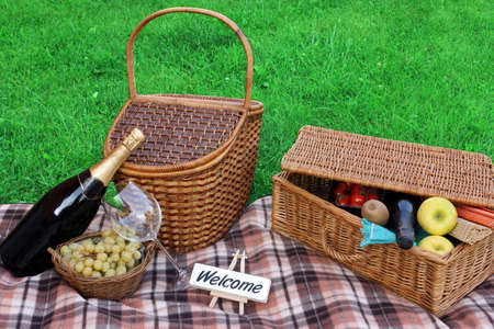 Summer Outdoor Picnic Scene On The Lawn With Sign Welcome, Wicker Basket, Hamper, Blanket, Grape, Wine, Champagne, Fruits Stock Photo