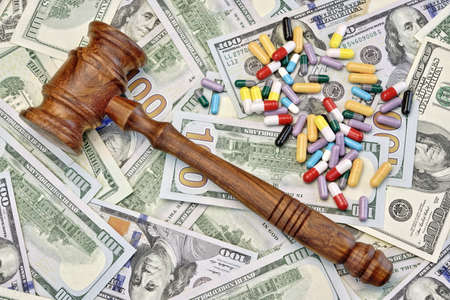 generic drugs: Wood Judges Gavel And Scattered Colorful Drugs On The Dollar Cash Background, Overhead View, Concept For Medical Negligence, Bail, Monetary Compensation, Drugs Falsification Stock Photo