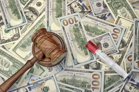 doctor with dollars: Wood Judges Gavel And Medical Syringe With Injection On The Dollar Cash Background, Overhead View