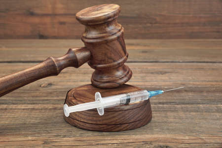 medical injection: Judges Gavel And Syringe Or Injection On Brown Wooden Table Background Close-up, Front View