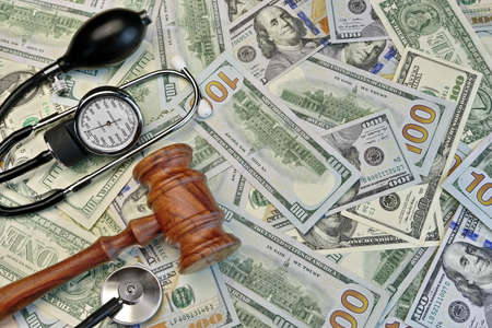malpractice: Wood Judges Gavel And Medical Tools On The Dollar Cash Background Stock Photo