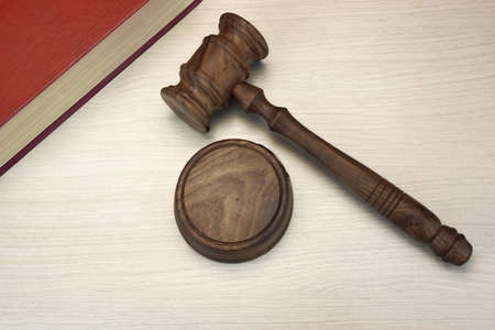 auctioning: Judges Or Auctioneer Gavel And Red Law Book On The White Wood  Background, Top View, Close-Up. Stock Photo