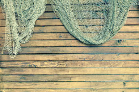 fishnet: Hanging Fishnet On The Rustic Wood Slats Wall Background. Gringe Wooden Background With Old Fish Net