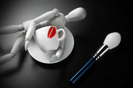 wood figurine: Empty Coffee Cup, Makeup Powder Brush and Wooden Mans Figurine On Black Wood Background Stock Photo