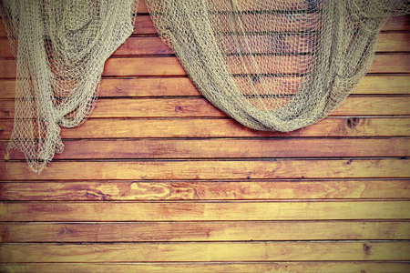 fish net: Hanging Fishnet On The Rustic Wood Slats Wall Background. Gringe Wooden Background With Old Fish Net