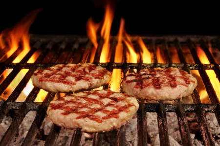 browned: Three Homemade Browned Burgers On The Hot Flaming BBQ Charcoal Grill With Bright Flames On The Black Background Stock Photo